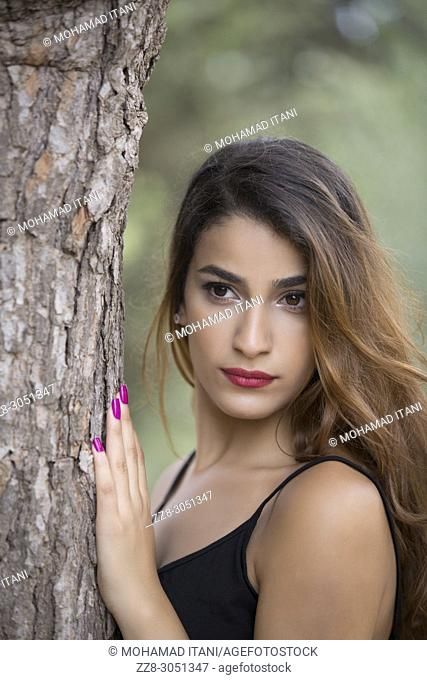 Beautiful young woman hand touching a tree looking away