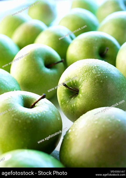 Green apples with drops of water, full frame