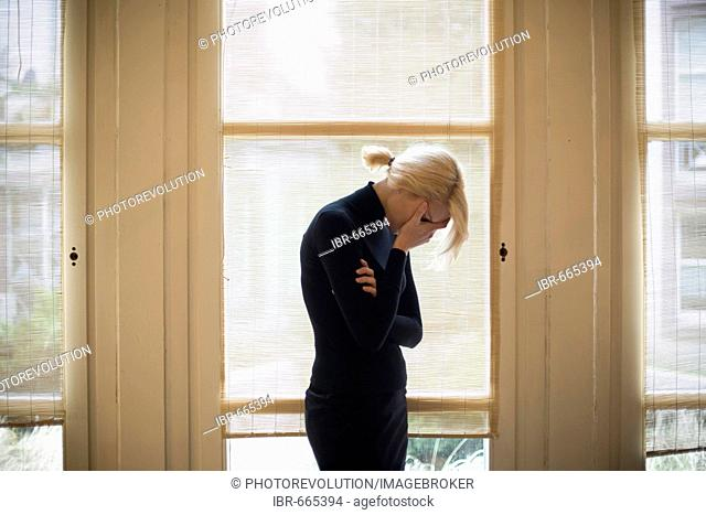 Sad blonde woman standing in front of large windows