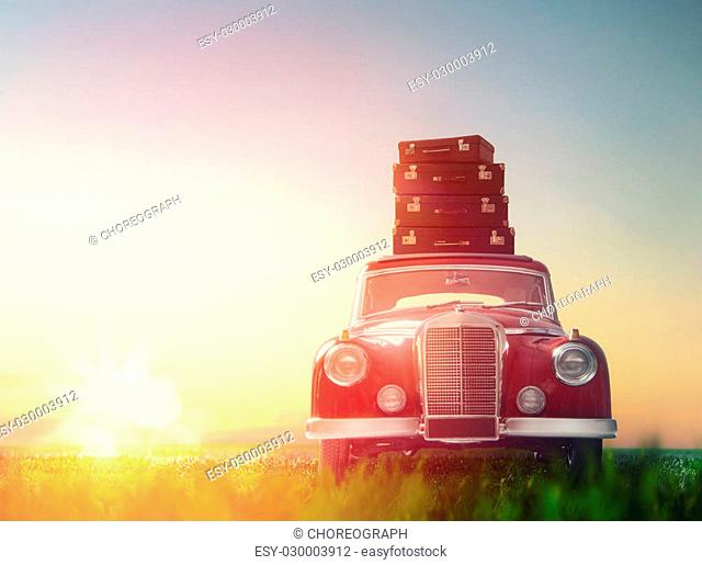 Toward adventure! The suitcases are on the roof of a vintage car