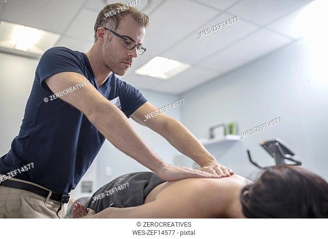 Physio massaging woman's back