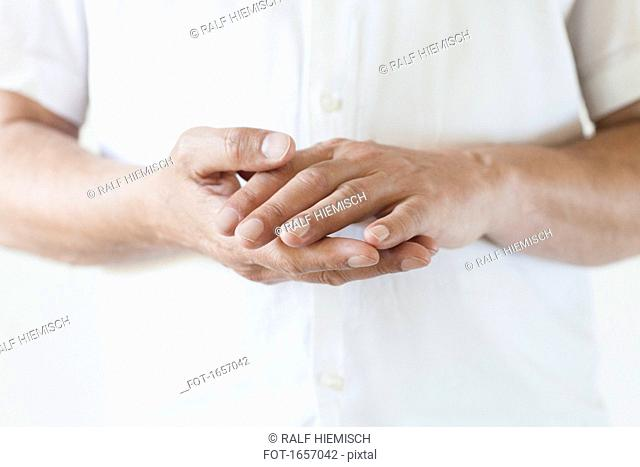 Midsection of man wearing white t-shirt with hands clasped