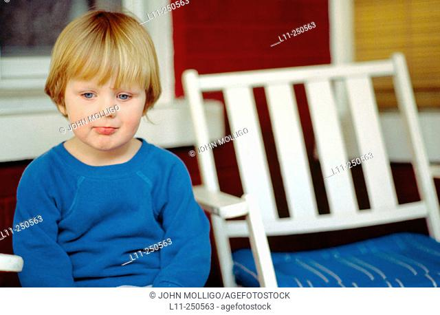 Young boy (4-6 years old) sitting on porch