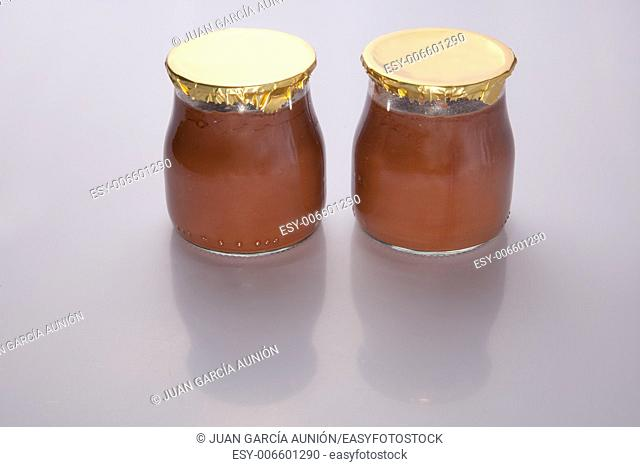 Chocolate truffle glass vessels with golden cap over white background