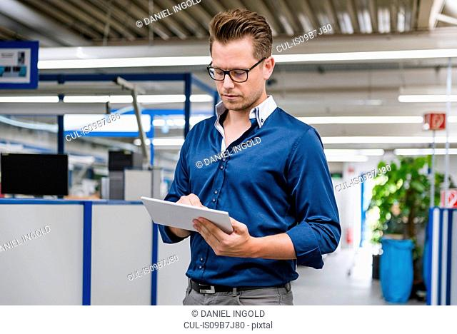 Factory manager looking at digital tablet in factory