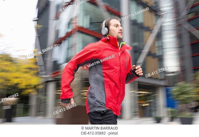 Man running with headphones past urban building