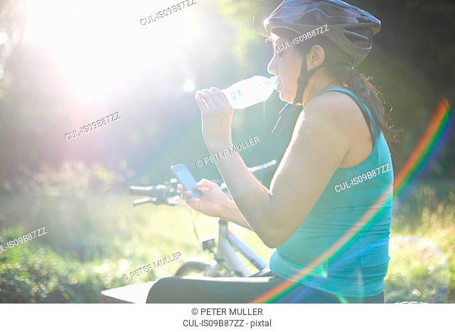 Cyclist taking break, using mobile phone