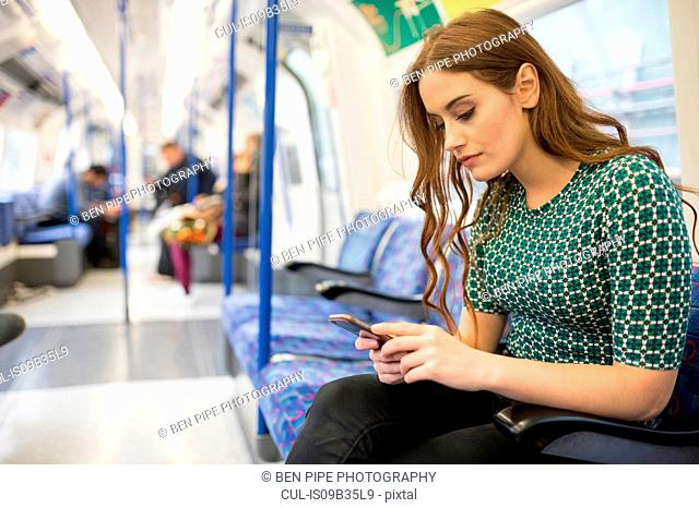 Woman on train looking at smartphone