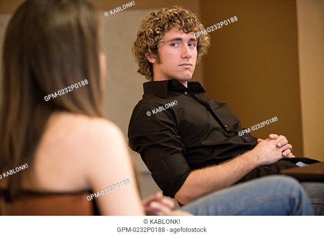 Young man relaxing with friend indoors, focus on background