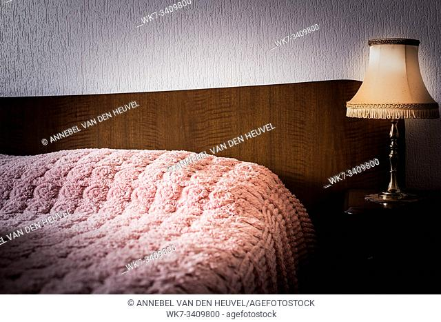 Vintage interior with antique night light, bed, wooden nightstand and wallpaper in bedroom retro design