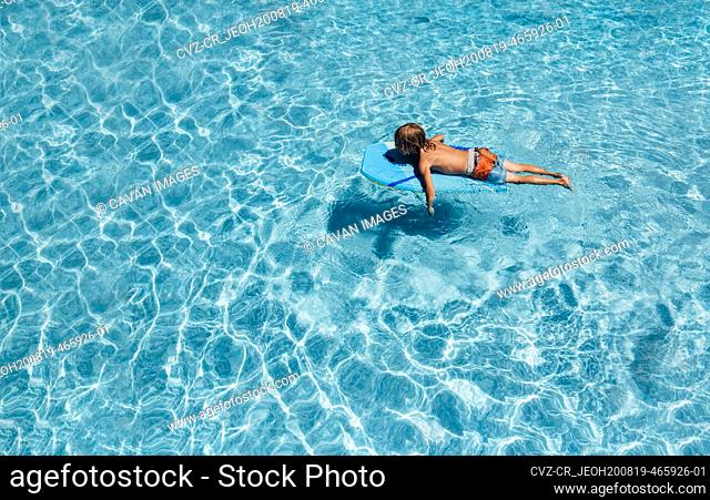 Young boy floating in pool on a summer day