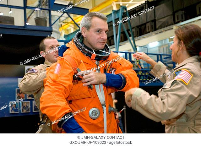 Astronaut Richard M. Linnehan, STS-123 mission specialist, gets help donning a training version of his shuttle launch and entry suit in preparation for an...