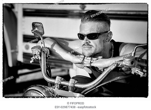 Tough guy with sparrow beard, undercut, black rip shirt and sun glasses lolling on his chopper motorcycle in front of a yellow, American school bus