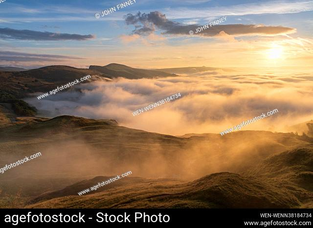 The view from Little mam Tor looking down Hope Valley with the light from the rising sun catching the swirling fog over the Derbyshire Peak District