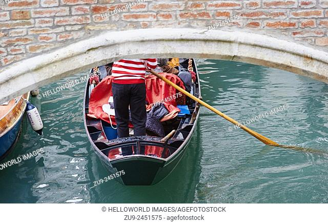 Gondolier in traditional red and white striped top rowing a gondola under a bridge, Castello, Venice, Veneto, Italy, Europe