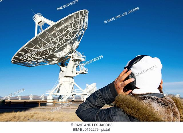 Hispanic technician listening to satellite in field