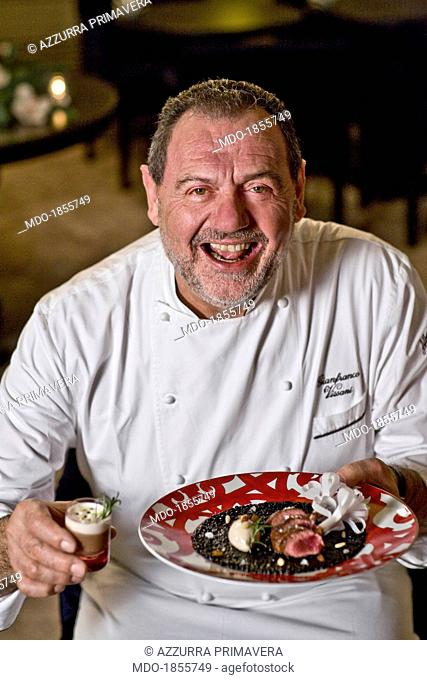 Italian chef Gianfranco Vissani smiling while showing a Christmas meal made by himself for a photocall shooted at his restaurant