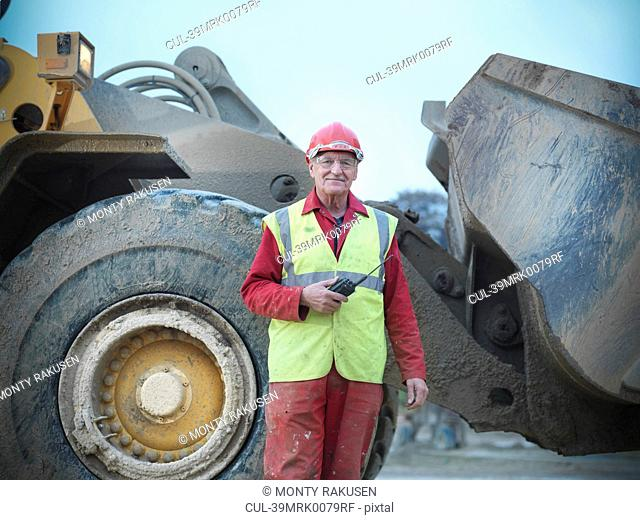 Construction worker standing with digger