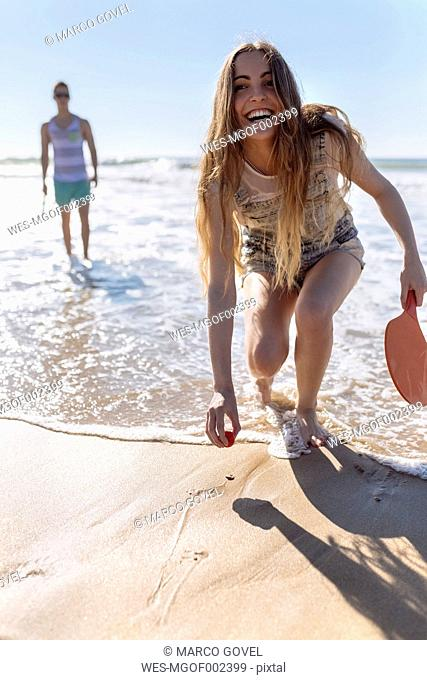 Laughing teenage girl playing beach paddles on the beach