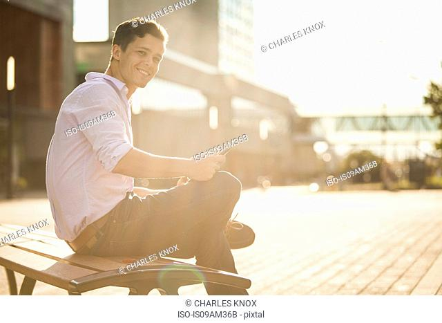 Portrait of young male higher education student sitting on bench using digital tablet
