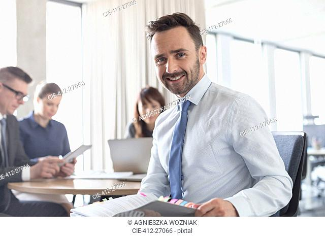 Portrait smiling brunette businessman with report in conference room meeting