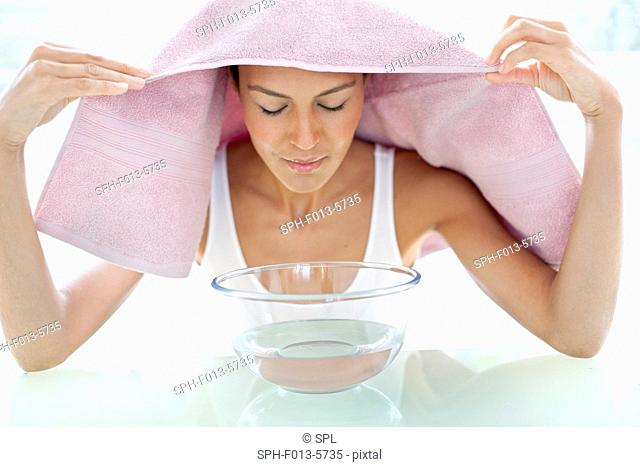 MODEL RELEASED. Young woman with a cold inhaling steam from a bowl
