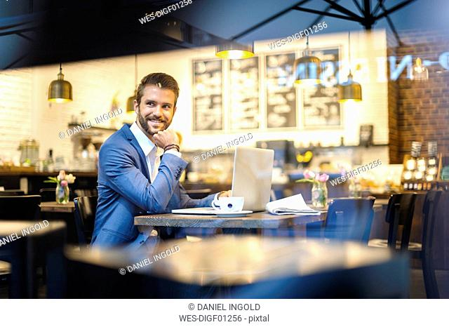 Smiling businessman with laptop in a cafe