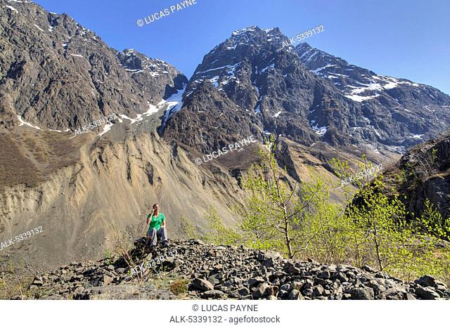 Female hiker talking on a cell phone along the Eklutna Lake Trial and Chugach Mountains, Chugach State Park, Southcentral Alaska, Spring, HDR