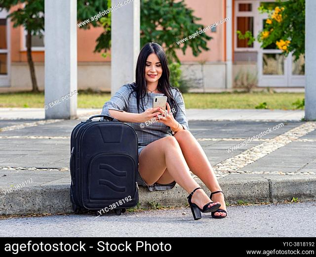 Young woman is going traveling sitting on roat street sidewalk