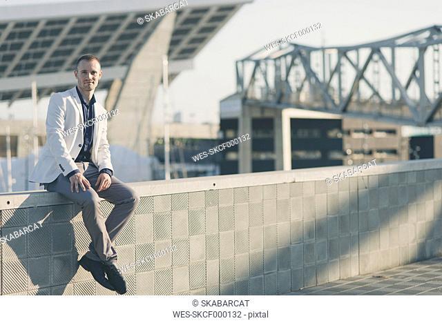 Fashionable businessman sitting on wall at sunlight