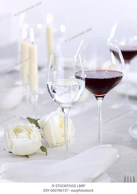 Glasses of red & white wine on table laid for special occasion