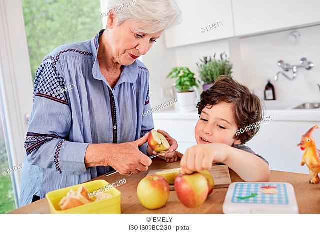 Grandmother and grandson preparing food in kitchen