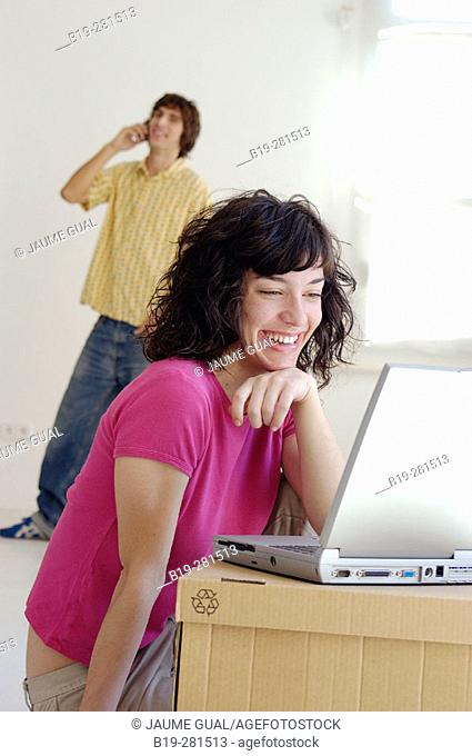 Couple moving home, the girl with laptop while the boy with mobile phone