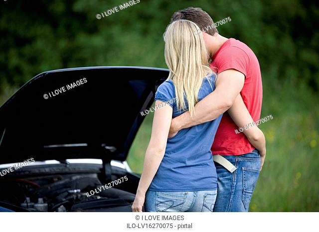 A young couple standing next to their broken down sports car, looking at the car engine