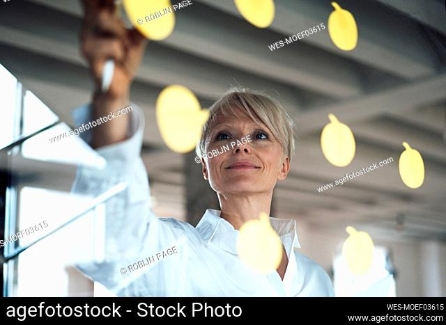 Businesswoman sticking adhesive notes on glass wall
