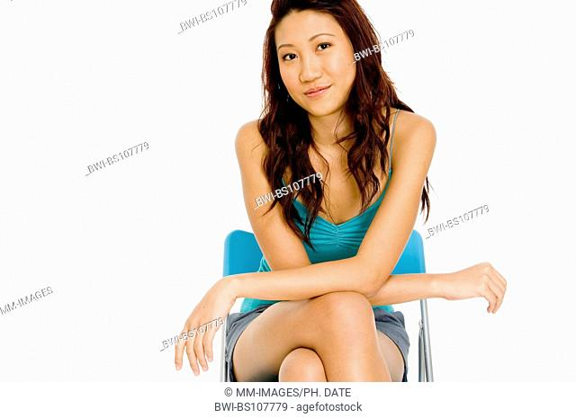 A beautiful young asian woman in a seated pose