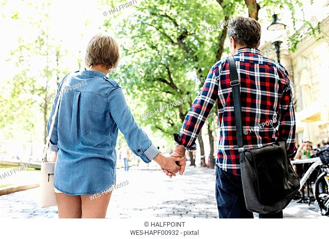 Back view of senior couple holding hands