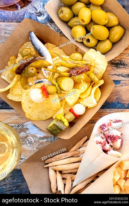 Tapas and pinchos. Spicy gildas with peppers, potato chips, olives, jamon on a wooden table in an outdoors cafe