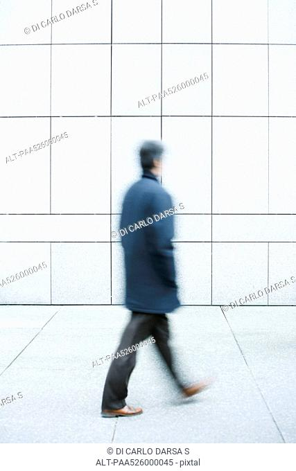 Man walking with hands in pockets down sidewalk