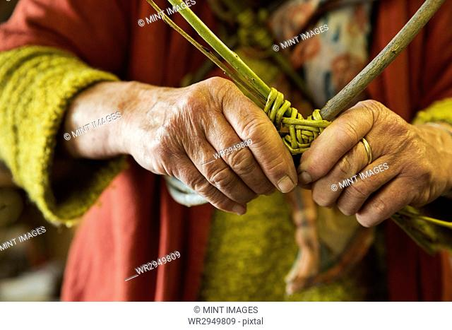 Close up of woman weaving a basket in a weaver's workshop