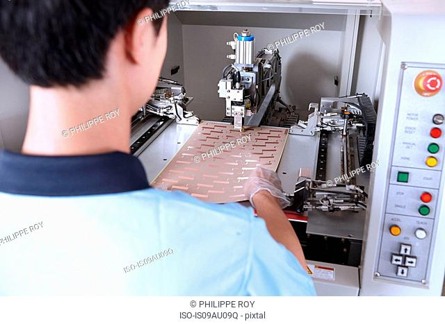 Over shoulder view of young man using cutting tool to make flexible circuits