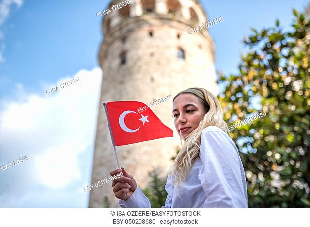Attractive young beautiful girl takes selfie and waves Turkish flag in front of Galata Tower,a popular landmark in Istanbul,Turkey