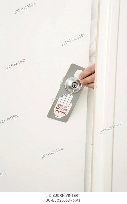 Hand putting Do Not Disturb sign on door