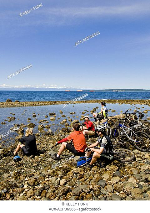 A group of mountain bikers rest at the Pacific ocean in Powell river, on the upper Sunshine coast of the Vancouver coast and mountain range, British Columbia
