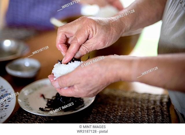 Close up of woman standing at a table in a kitchen, making sushi