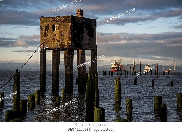 Concrete structure and wooden pilings along the riverwalk with ships in the background; Astoria, Oregon, United States of America