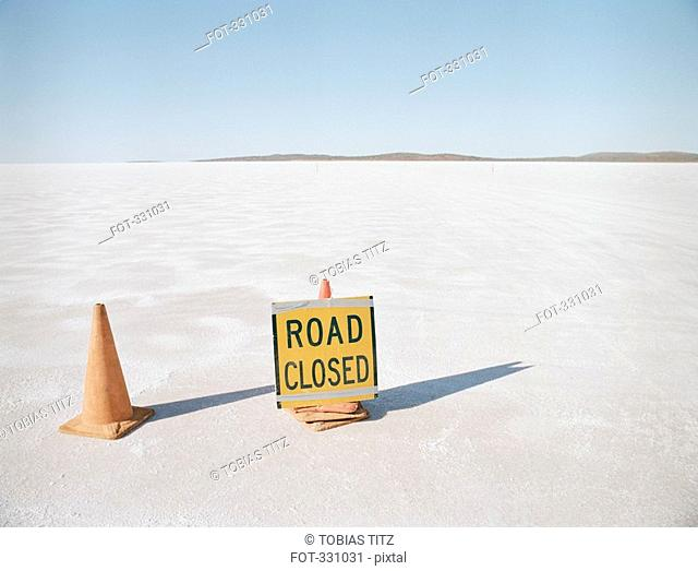 'Road Closed' sign and traffic cones on salt flat