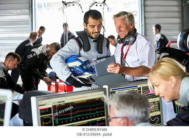 Manager and formula one driver with digital tablet talking in repair garage