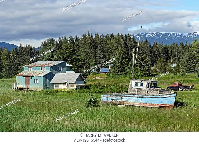 Rustic wooden boat and home on the grass shore near ferry dock, Southeast Alaska; Gustavus, Alaska, United States of America