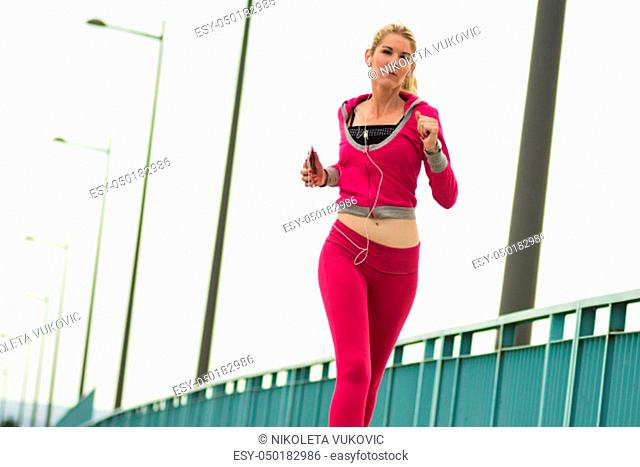 The attractive blond hair woman is jogging in pink sportswear outdoors